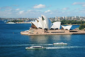 Sydney opera house with ferrys in foregournd — Stock Photo