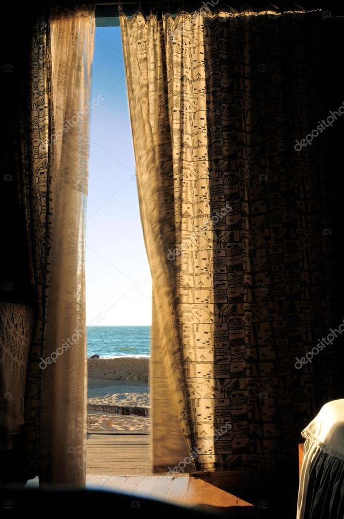 View of the beach through the open door — Stock Photo #15002005
