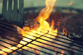 A beef burger being grilled on a barbecue — Stock Photo