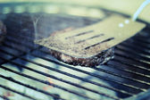 A beef burger on a barbecue — Stock Photo