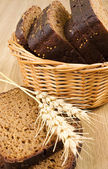 Basket with bread and wheat on the table — Stock Photo