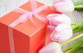 bouquet of tulips, gift box on a table — Stok fotoğraf