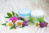 Containers with cream and wild flowers — Stock Photo