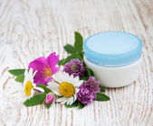 Container with cream and wild flowers — Stock Photo