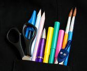 School supply in the black pocket — Stock Photo