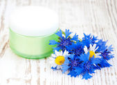 Container with cream and cornflowers — Stock Photo