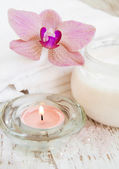 Moisturizing cream with pink orchids — Stock Photo