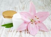Face cream with lily flowers — Stock Photo