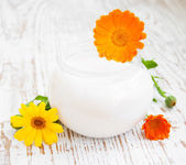 Face cream and calendula flowers — Stock Photo