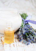 Container with cream, massage oil and lavender — Stock Photo
