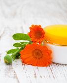 顔のクリームとキンセンカの花 — ストック写真