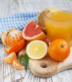 Citrus fruits and fresh orange juice — Stock Photo