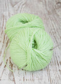 Green yarns and crotchet hook — Stock Photo