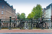 Couples of bikes over the canal of Amsterdam — Stock Photo