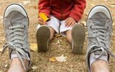 Sneakers front view of father sitting on field with his son — Stock Photo