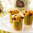 Chocolate chip muffins on white plate and green striped tableclo — Stock Photo #15474421