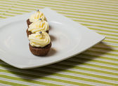 Chocolate cupcakes with silver sprinkles on top on white plate — Foto Stock