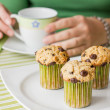 Nice girl with a cup and chocolate chip muffin at breakfast — Stock Photo