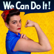 Young woman posing as working girl like the original poster of Rosie the Riveter, year 1943 - Stock Photo