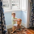 Royalty-Free Stock Photo: Little boy riding on vintage rocking horse