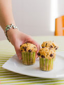 Nice girl hand taking chocolate chip muffin at breakfast — Stock Photo