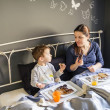 Mother and son having breakfast in bed — Stock Photo