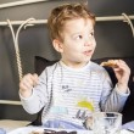 Child having breakfast in bed — Stock Photo