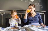 母亲和儿子在床上吃早餐 — 图库照片