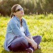 Smiling woman sunbathing sitting in a field — Stok fotoğraf