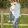 Pregnant mother sitting her son on a wooden fence in a field — Stock Photo #24218867