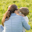 Cute son kissing to his mother sitting in a field — Stock Photo