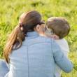 Cute son kissing to his mother sitting in a field — Stock Photo #24512973