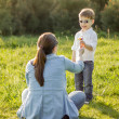 Son giving a bouquet of flowers to his mother in a field — Stock Photo