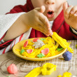 Child playing with spaghetti dish made with plasticine - Stock Photo
