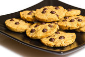 Chocolate chip cookies on a black plate isolated on white backgr — 图库照片