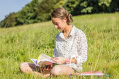 Beautiful young student reading a book in the park — Stock Photo
