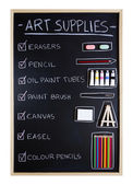 Art supplies over blackboard background — Stock Photo