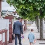 父および幼い息子は学校に通りを歩いて — ストック写真