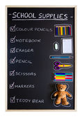 School supplies over blackboard background — Stok fotoğraf