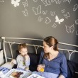 Mother and son having breakfast in bed — Stock Photo #30571621