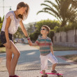 Young girl and cute kid with skateboards outdoor — Stock Photo #31818979