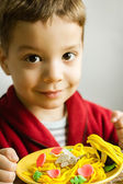 Portrait of child with plasticine spaghetti dish — Stock Photo