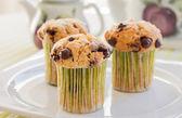 Chocolade chip muffins op witte plaat en groene gestreepte tableclo — Stockfoto