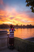Young man shooting the sunset in Buen Retiro park — Stockfoto