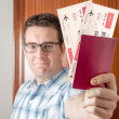 Happy man showing boarding pass and passport — Stock Photo