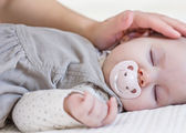 Hand of mother caressing her baby girl sleeping — Foto Stock