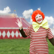 Clown with big bow tie over circus tent background — Stock Photo #37125315