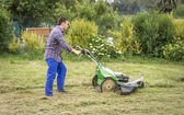 Young man mowing the lawn with a lawnmower — Stock Photo