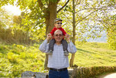 Grandfather holding grandchild on his shoulders — Stock Photo