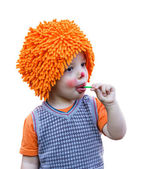 Clown child eating a lollipop on white background — Stock Photo